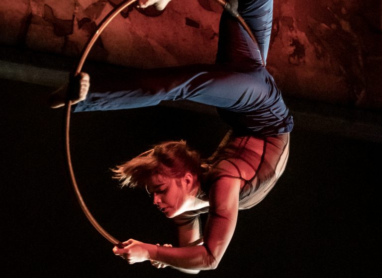 The 7 Fingers performer hanging from a hula hoop in mid air