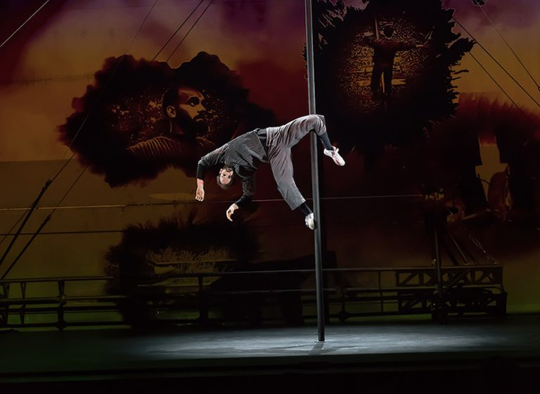 The 7 Fingers performer hanging sideways on a pole