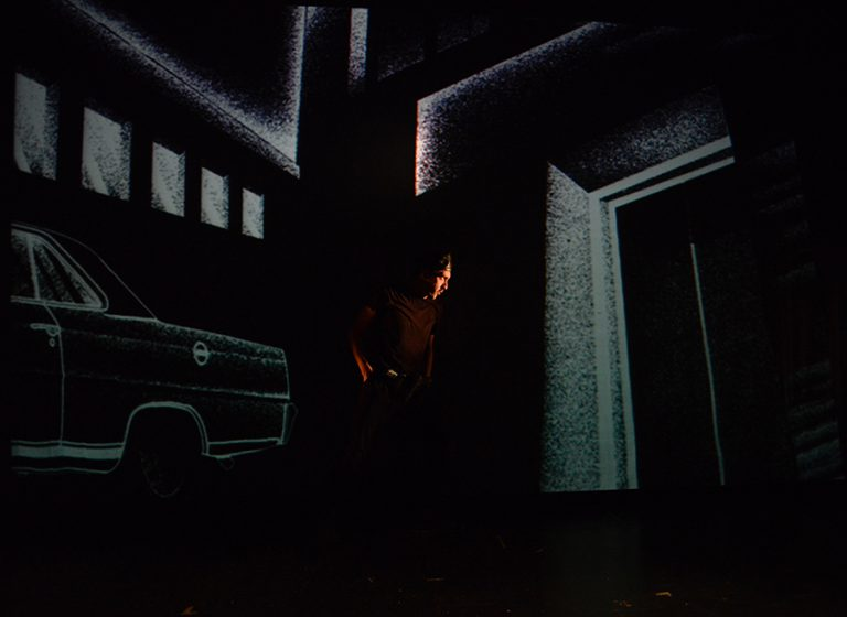 Man standing in middle of dark scene with projections of a sketched scenery of a car and buildings behind him in Plata Quemada