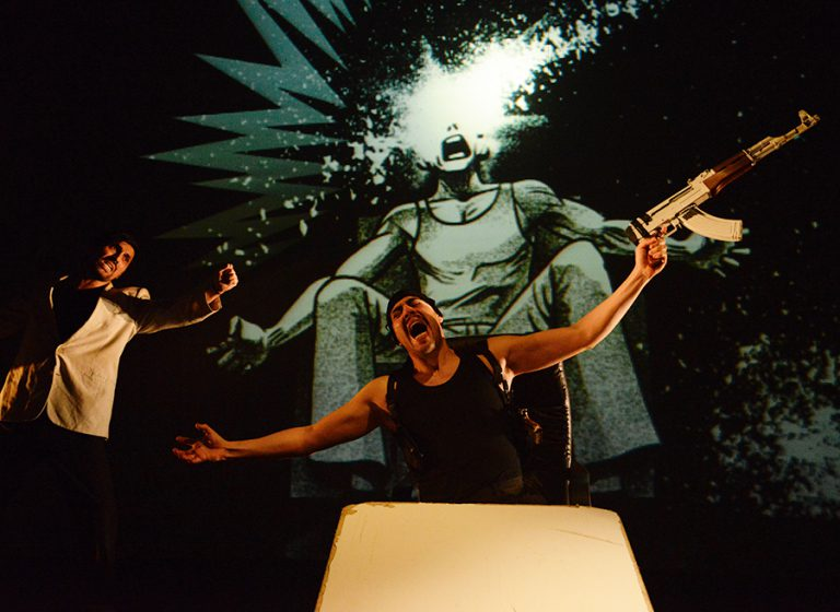 Man pointing gun at another with outstretched arms in Plata Quemada. Sketched background projected of cartoon person exploding.