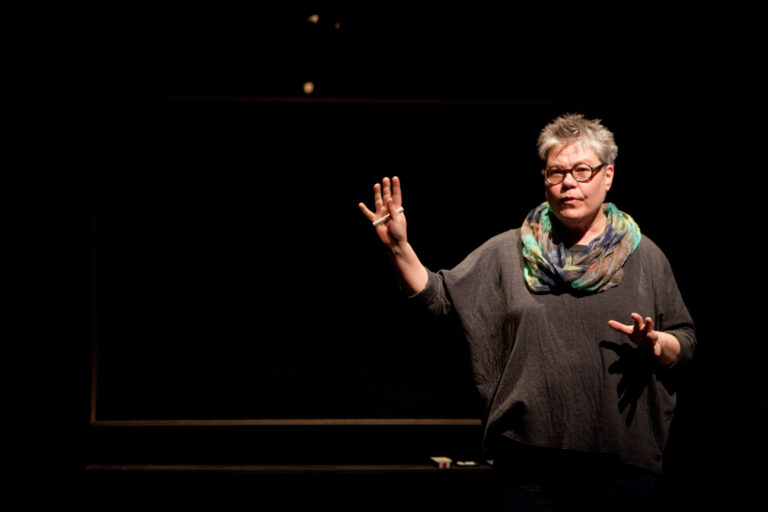 Alanna Mitchell performing a monologue on a dark stage in front of a blackboardin Sea Sick