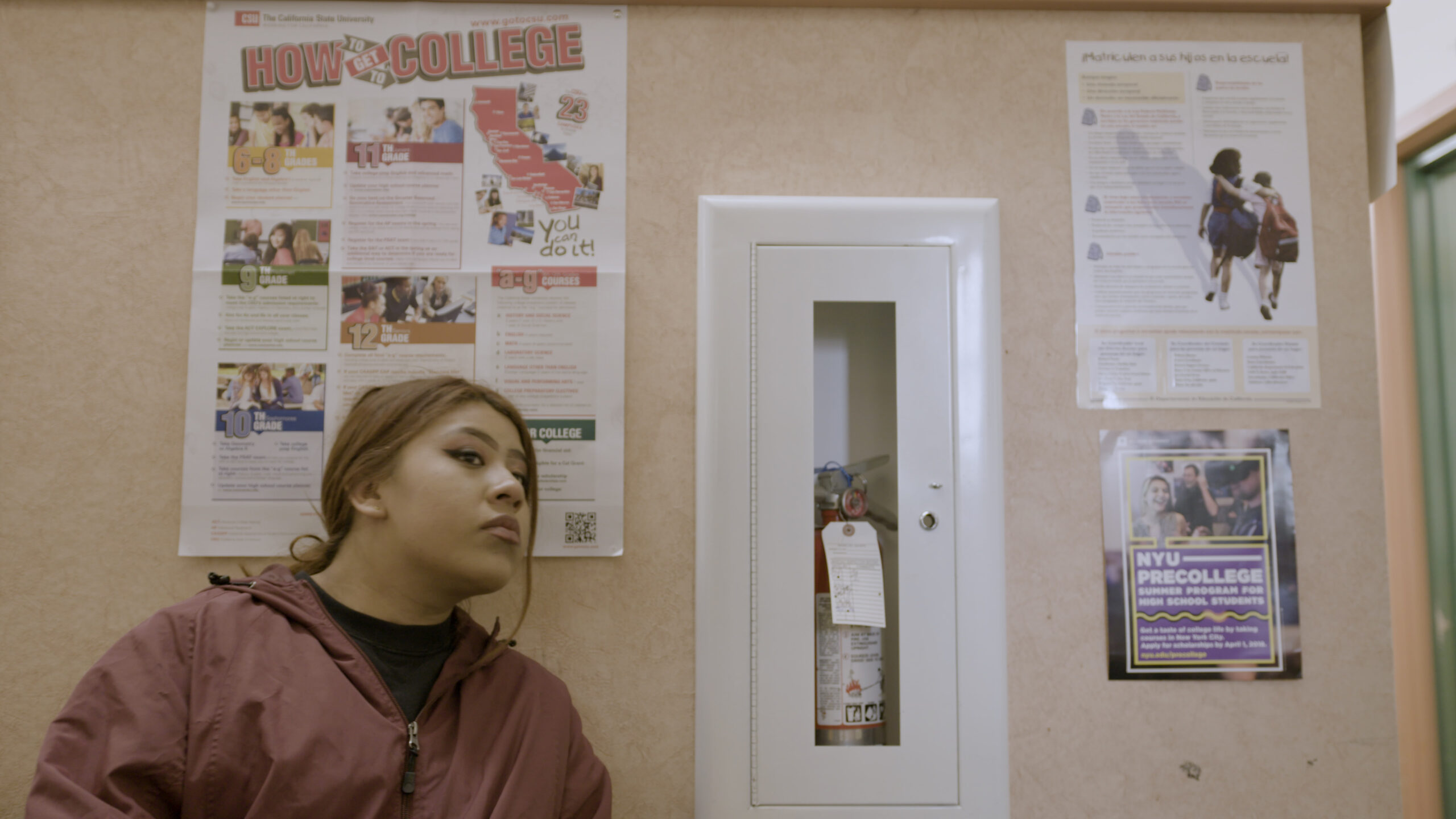 Girl sitting in front of a wall with college information posters behind her