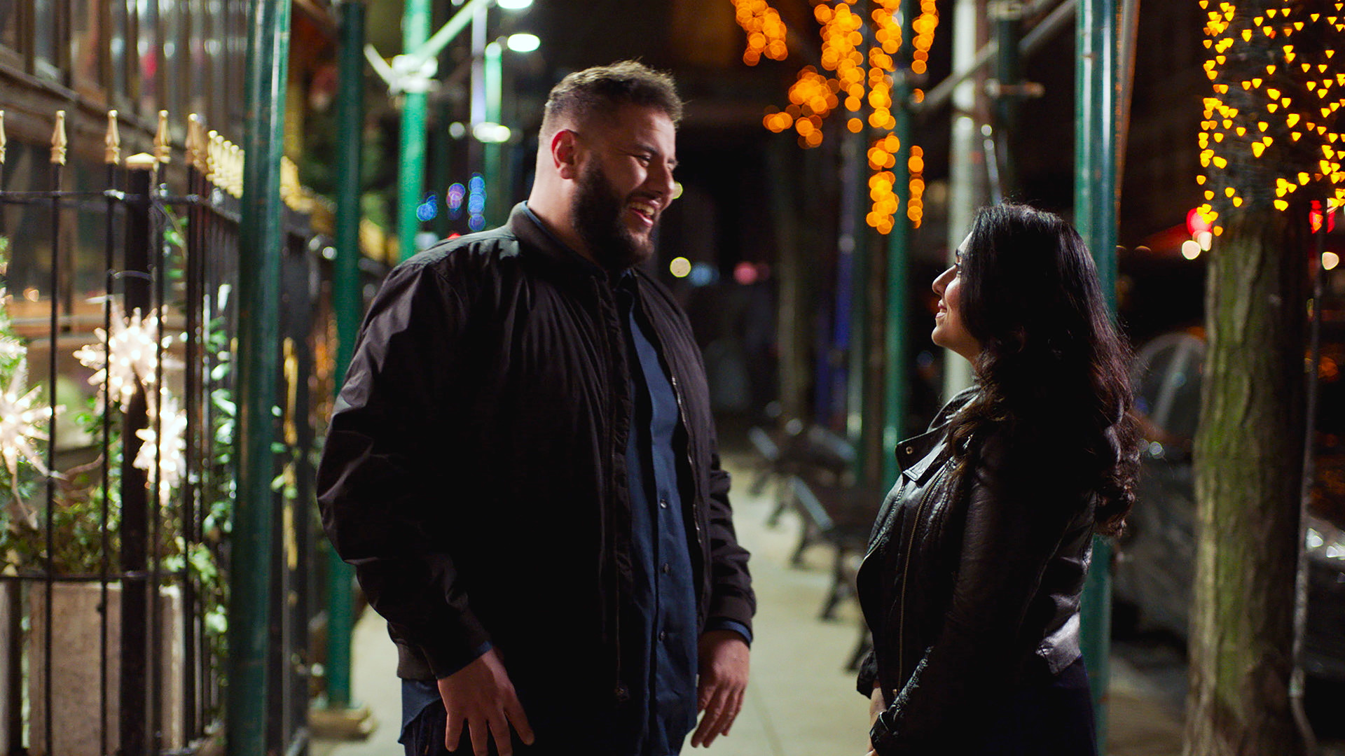Two people smiling and talking outside at night