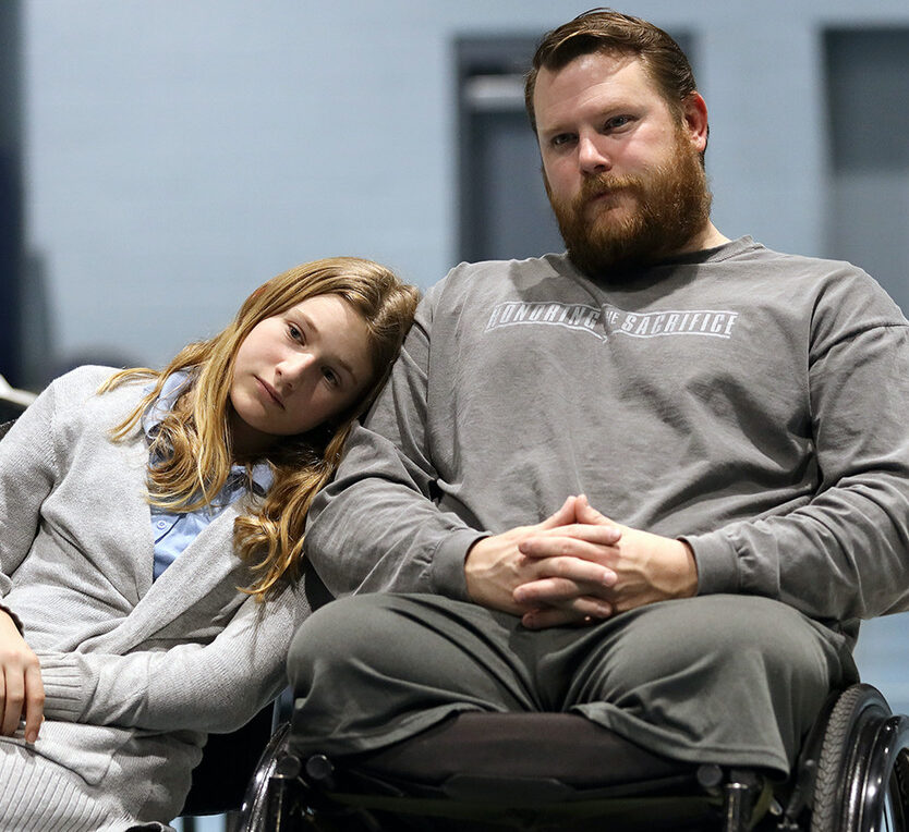 Two people in wheelchairs, one resting their head on the other