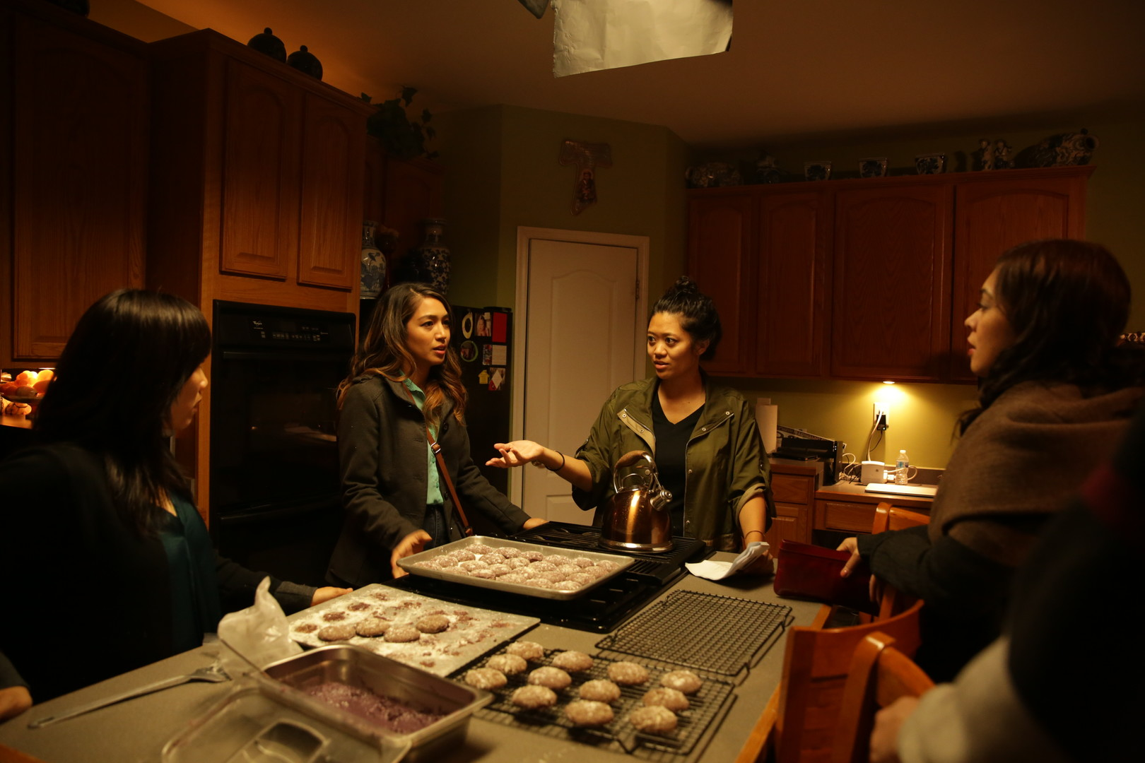 Four people standing around talking in a kitchen
